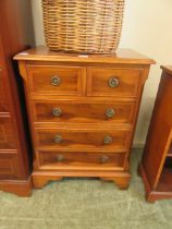 A modern yew veneered chest of two short over three long drawers