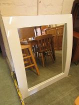 A modern white framed bow fronted mirror