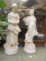 A pair of painted garden ornaments of young ladies