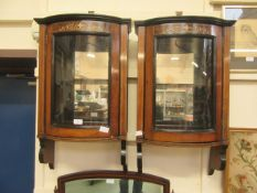 A pair of Edwardian rosewood inlaid mirror back wall hanging bow fronted cabinets (A/F)
