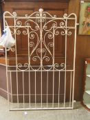 A white painted wrought iron garden gate