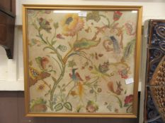 A framed and glazed possible 18th century crewel work panel depicting birds, flowers,