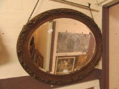 An ornate oval bevel glass mirror