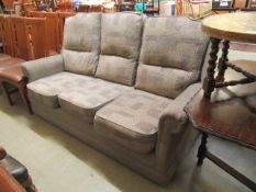A modern three seater settee upholstered in a grey cut fabric