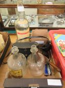 A tray containing three large spirit bottles, two pairs of binoculars, box with fossils,