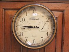A reproduction Westminster wall clock with humidity and temperature dials