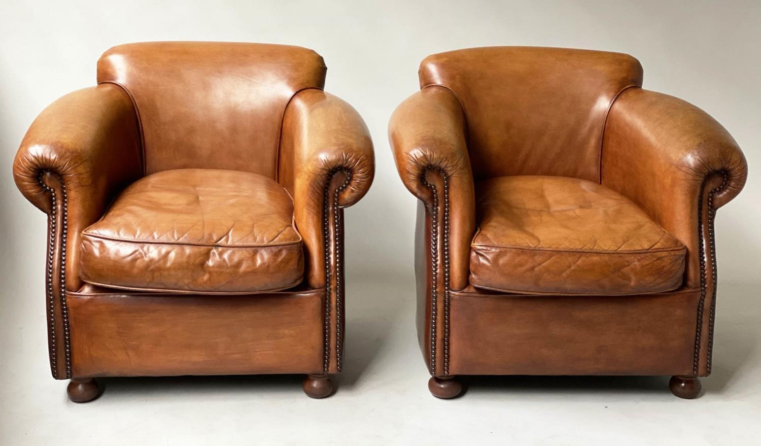 CLUB ARMCHAIRS, a pair, tobacco leaf brown leather and brass studded with scroll arms, 83cm W. (2)