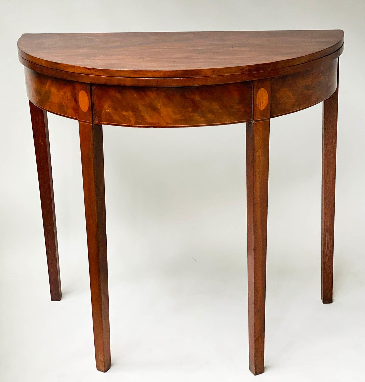 TEA TABLE, George III flame mahogany with demi lune foldover top and satinwood paterae headed