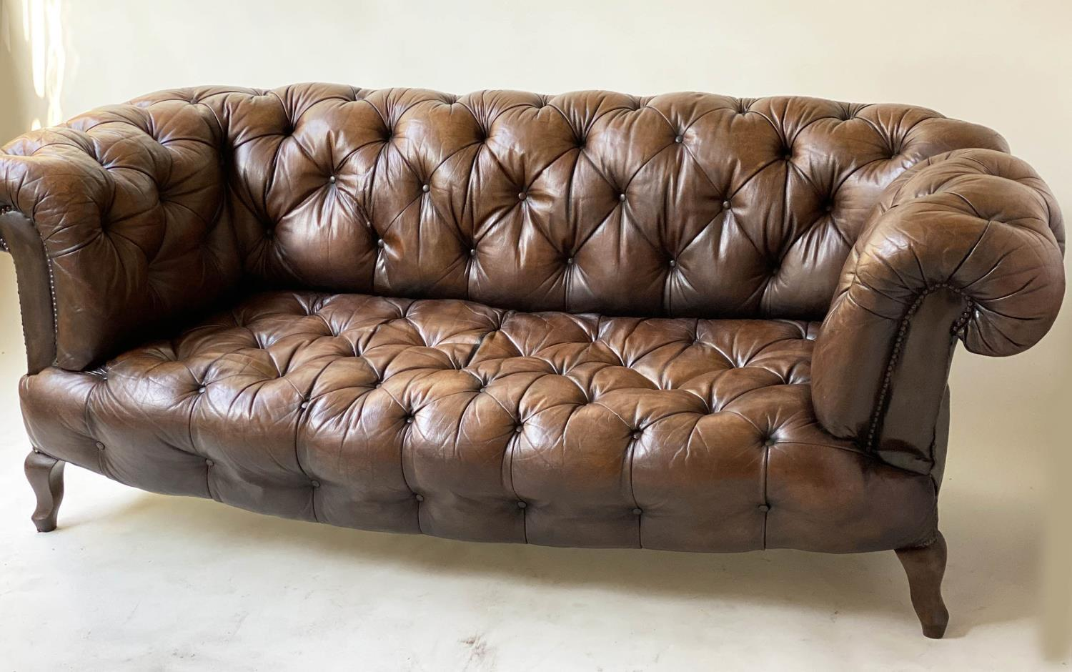 CHESTERFIELD SOFA, early 20th century Edwardian aged and faded brown leather with horsehair buttoned