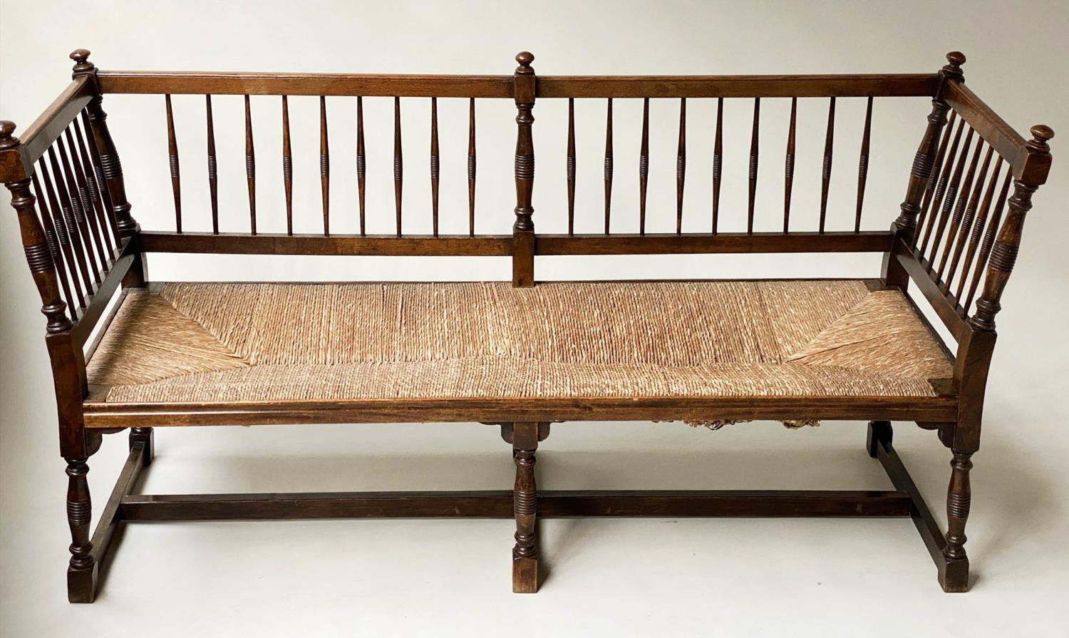 HALL BENCH, 19th century English oak with spindle back rush seat and stretchered turned supports,