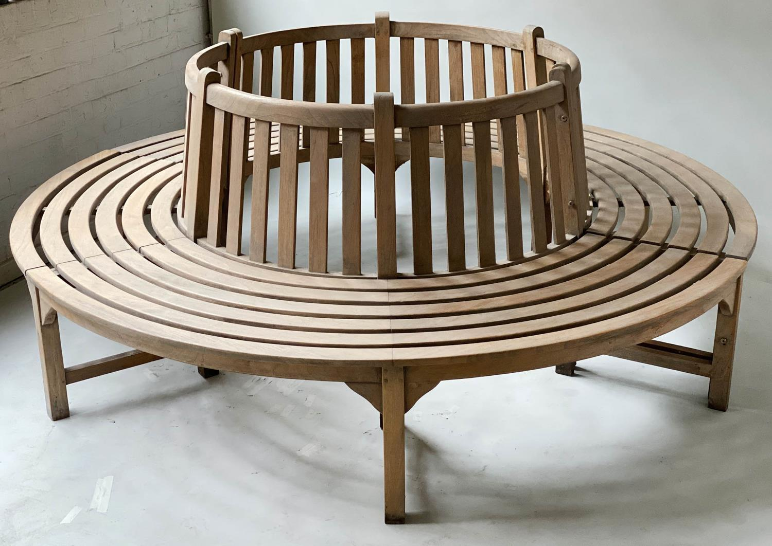 TREE BENCH, weathered teak and slatted in two sections of concentric slats and raised back rest,
