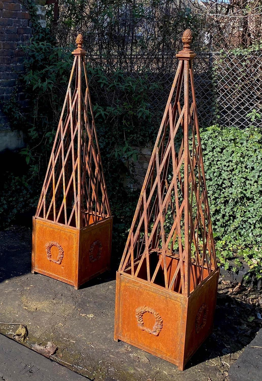 PLANTERS, a pair with associated obelisks, oxidised finish, 184cm H approx. (2)