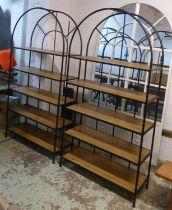 MAISONS DU MONDE ARCH SHAPED SHELVING UNITS, a pair, black metal framed, each enclosing wooden