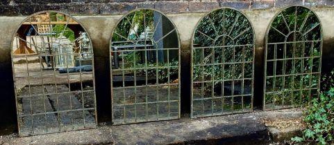 ARCHITECTURAL GARDEN MIRRORS, a set of four, aged metal frames, 78cm x 49cm. (4)
