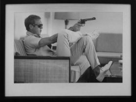 AFTER JOHN DOWNING, Steve McQueen with gun, framed and glazed, 73cm x 53.5cm.