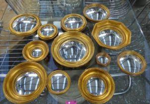 CONVEX WALL MIRRORS, a set of twelve, Regency style, various sizes, gilt frames, 27cm diam at