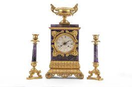 Trittico composto da orologio di appoggio e due candelabri in bronzo dorato e ametista