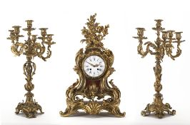 Trittico composto da una pendola da tavolo e due candelabri in bronzo dorato