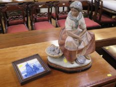 A Lladro figure of a fisher-woman, seated holding a pair of balances with a basket of fish beside