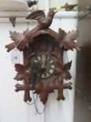A carved softwood Swiss cuckoo clock, the twin train movement with bellows and coil gong, retail