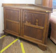 A oak corner side cabinet, with a pair of panelled doors on bracket feet, 123 cm wide, 60 cm deep,