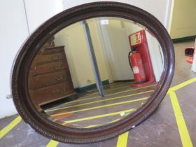 A 1920s oval mirror, with bevelled plate, within a cavetto beaded frame, 100 cm x 70 cm