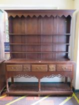 A George III style stained oak dresser and rack, the stepped rack over a base with five frieze