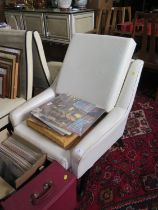 A 1950s cream faux leather armchair, the reclined button back on ebonised square moulded legs