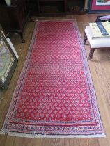 A Persian Sarouk Mir design runner, with allover boteh design on a red ground, 300 x 109 cm