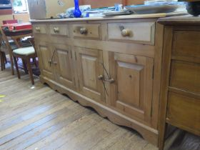 A pine dresser base, with four short drawers over two pairs of panelled doors on a shaped plinth