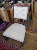 An Edwardian walnut lady's fire side chair, with carved top rail, button back and ring turned
