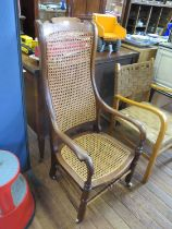 A Victorian elm and cane high back armchair, with ring turned legs joined by stretchers, on later