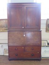 An early 19th century mahogany secretaire cabinet, the pair of panelled doors enclosing adjustable