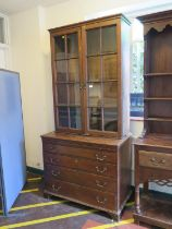 A George III oak chest of drawers, with associated bookcase, the bookcase with glazed doors and