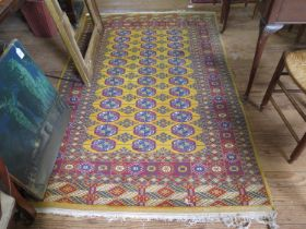 A Bokhara rug, the three rows of guls on a gold colour ground within a multiple border, 206 x 128 cm