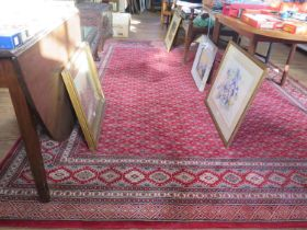 A Belgian Afghan design carpet, the red ground with an all-over bow design within a multiple border,