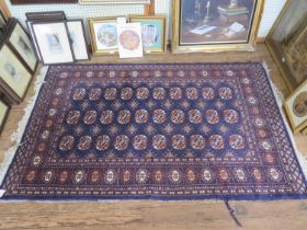 A Bokhara style rug, with three rows of guls on a blue ground within a multiple border, 192cm x