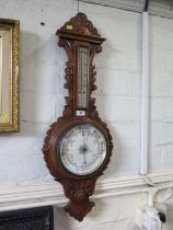 A carved oak banjo barometer, with thermometer and aneroid dial, 87 cm high