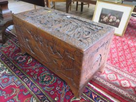 A Chinese camphorwood chest, the lid carved with figures looking out to sailing vessels, 93 x 45 cm,