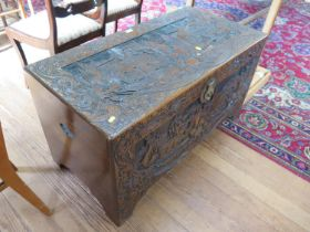 A Chinese carved camphorwood chest, the hinged lid depicting figures in gardens, within a dragon