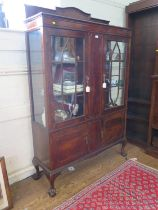 A 1930s mahogany display cabinet, the raised back over a pair of glazed doors and panelled centre