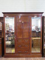 An Edwardian chevron banded mahogany compactum wardrobe, the central panelled door enclosing a shelf