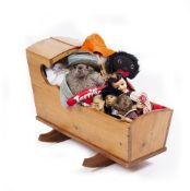 A PINE CHILD'S ROCKING CRIB 85cm x 32cm together with a stuffed Paddington Bear and further dolls