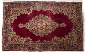 AN ORIENTAL RED GROUND RUG with decorative flower ornament to the central cartouche and banded