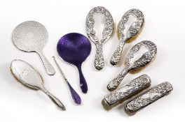 AN EARLY 20TH CENTURY ART NOUVEAU SILVER BACKED DRESSING SET to include four brushes and a mirror, a