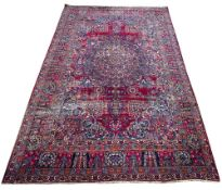 AN EARLY TO MID 20TH CENTURY MIDDLE EASTERN RED GROUND CARPET with a central stylised flower motif