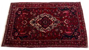 A MODERN ORIENTAL RED GROUND RUG with floral decoration to the central field and within a triple