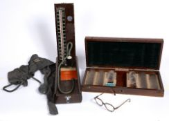 AN EARLY 20TH CENTURY CASED SET OF OPTICIANS EYE TESTING LENSES by Millikin & Lawley, the mahogany
