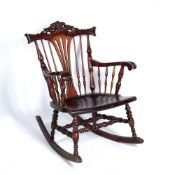A VICTORIAN STYLE MAHOGANY ROCKING CHAIR with a carved crest and spindle supports, 64cm wide x