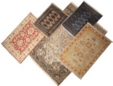 A MODERN ORIENTAL CREAM GROUND RUG with central floral decoration within a multiple banded border,